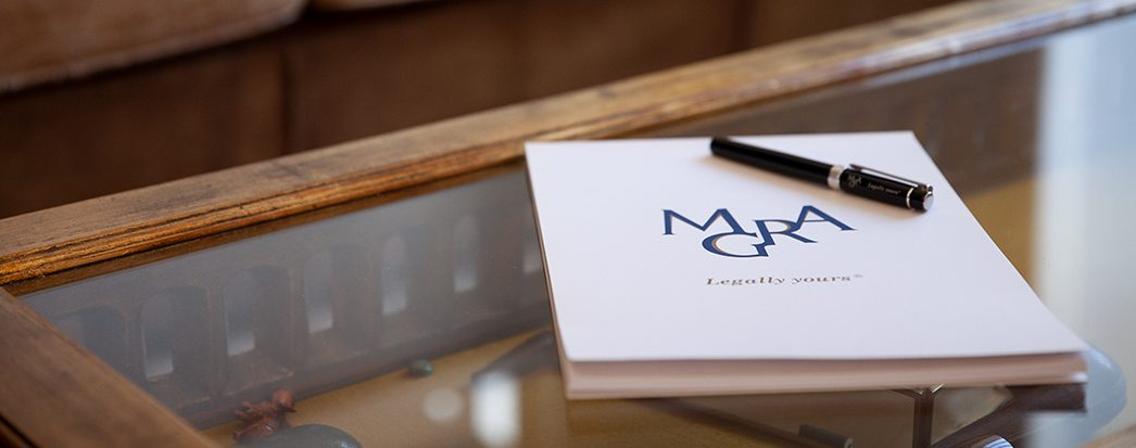 MGRA Advogados notebook with Mgra logo and a pen on the table